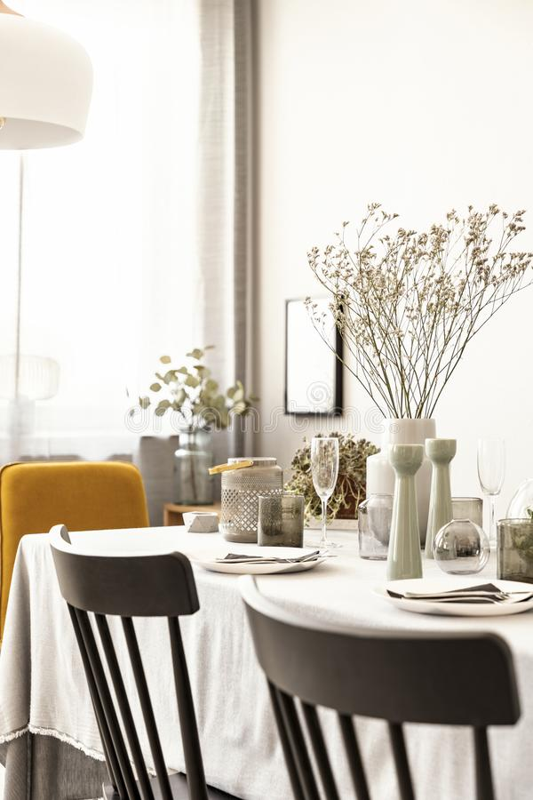 Chairs and table with flower and tableware in a dining room interior. Real photo. Close-up of chairs and table with flower and tableware in a dining room royalty free stock photos