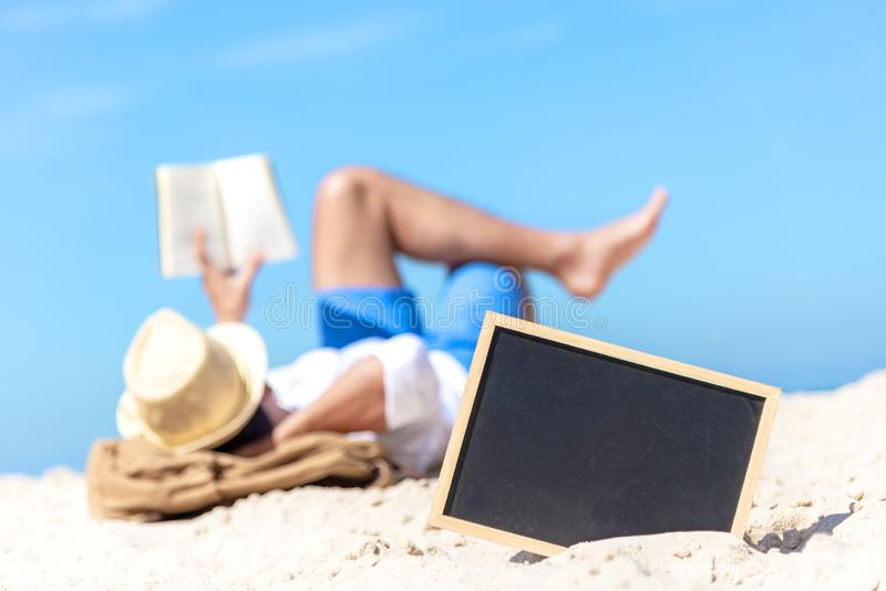 Close up of a chalkboard on the sand of a beach, background happy smiling caucasian tourist asian young man relax and reading book royalty free stock images