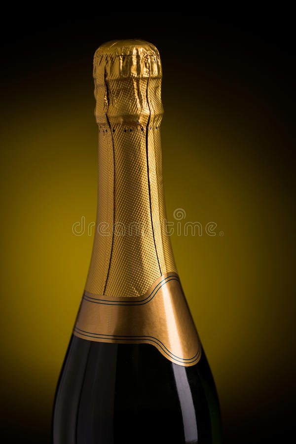 Close up of champagne bottle with blank label. Drink, alcohol, advertisement and holidays concept - close up of bottle of champagne with blank golden label over stock image