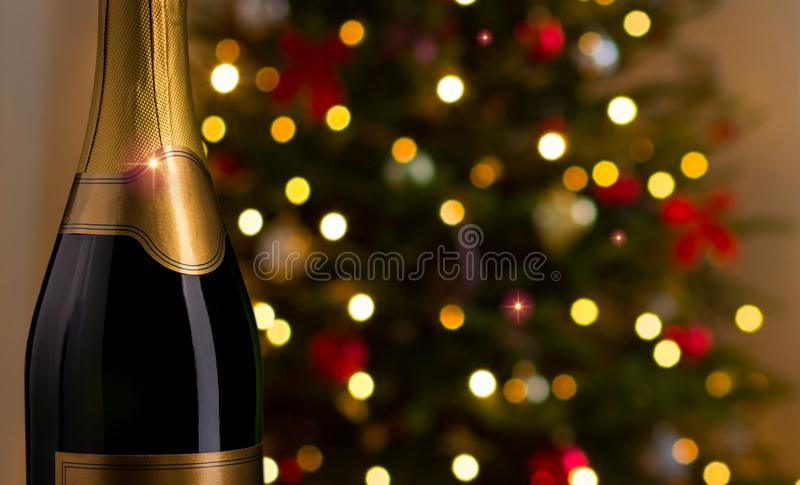 Close up of champagne bottle on christmas. Drink, alcohol, advertisement and holidays concept - close up of bottle of champagne with blank golden label over stock image