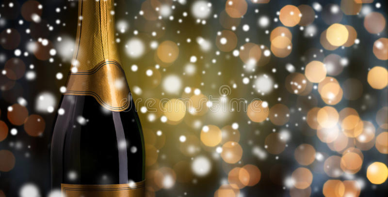Close up of champagne bottle with golden label. Drink, alcohol, christmas, new year and winter holidays concept - close up of bottle of champagne with blank royalty free stock photo
