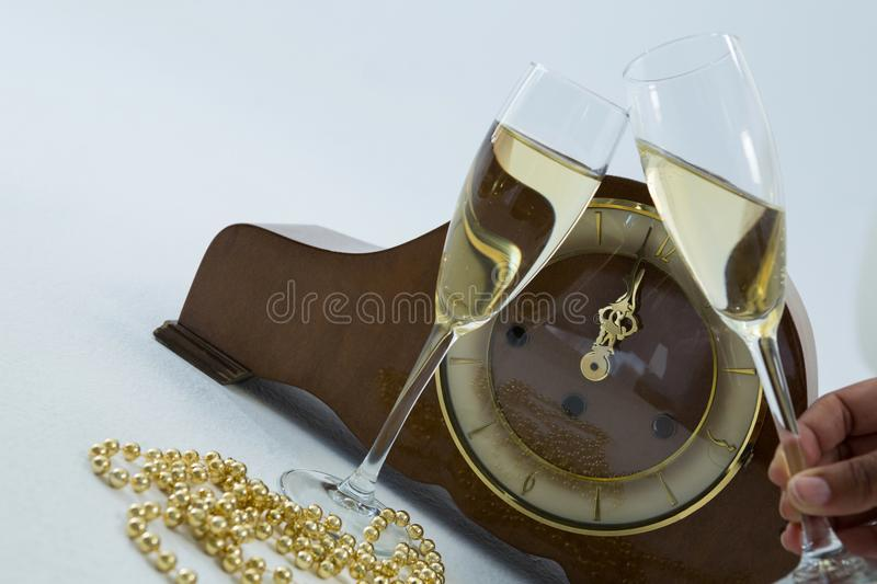 Champagne glass and clock on white background. Close-up of champagne glass and clock on white background stock image