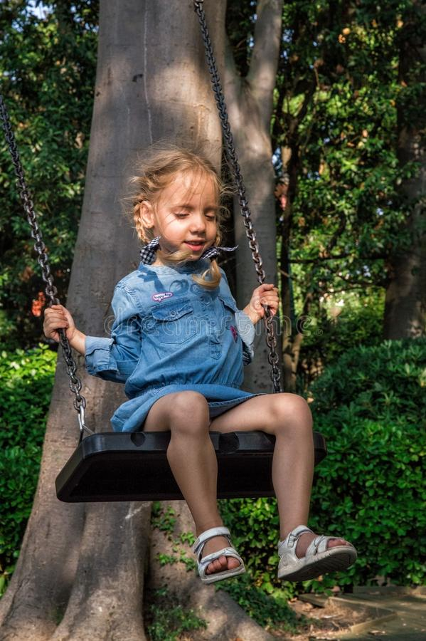 Close up. Charming girl in a blue dress riding on a swing. Close up. Playground in Venice. Charming girl in a blue dress riding on a swing royalty free stock image