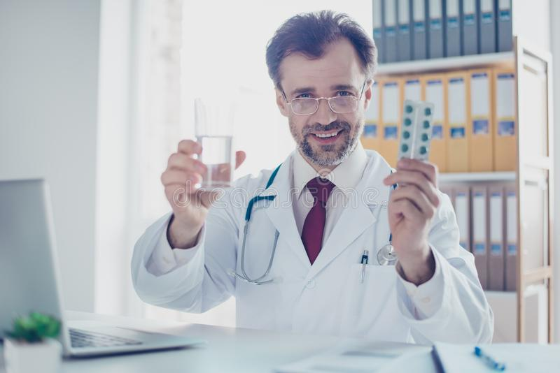 Close up of cheerful doc recommending the pills and glass of water, he is in formal wear and white coat on top royalty free stock photography