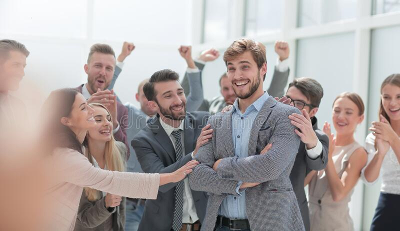 Cheerful employees congratulating a colleague on the promotion royalty free stock photo