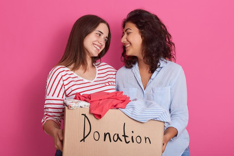 Close up of cheerful helpful volunteer girls standing isolated over pink background, holding box with different clothes. Full box stock photography