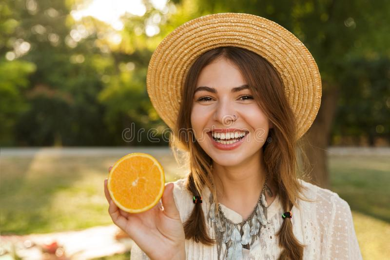 Close up of cheerful young girl in summer hat spending time at the park stock photography