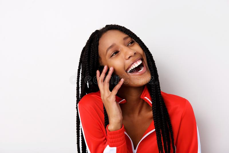 Close up cheerful young woman with braided hair talking on mobile phone and laughing. Close up portrait of cheerful young woman with braided hair talking on royalty free stock image