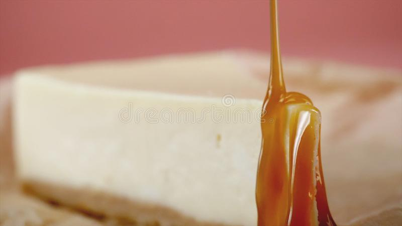 Close-up of cheesecake is poured sweet sauce. Frame. Appetizing cheesecake artfully watered with sweet caramel. Concept royalty free stock photos