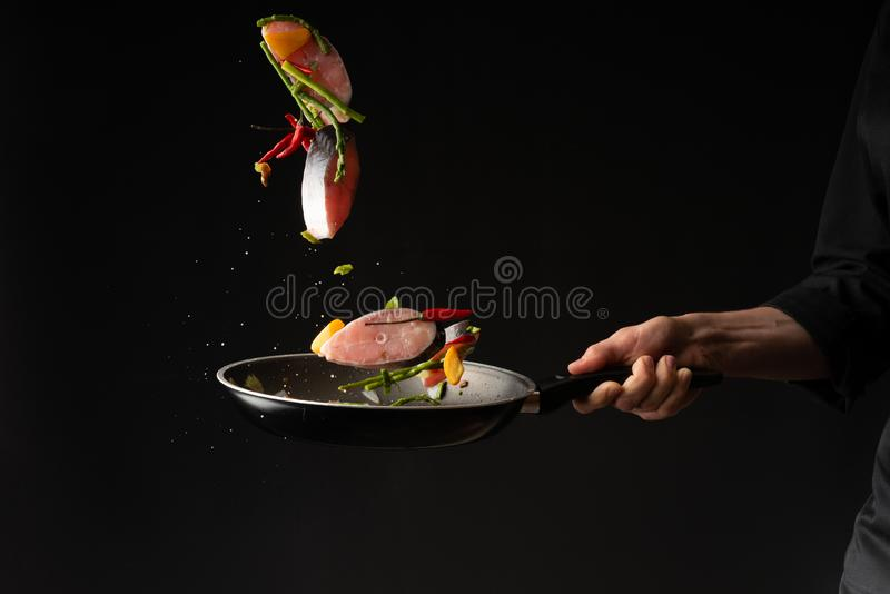 Close-up. Chef cook fry fish with vegetables on a griddle on a black background. horizontal photo. sea food. healthy food. stock image