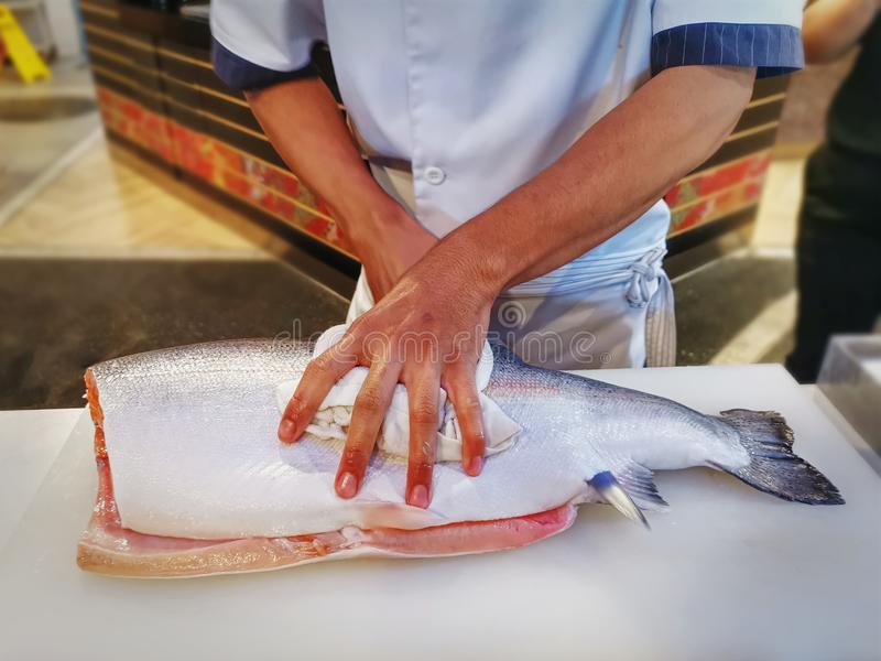 Chef Filleting Salmon on Table at Japanese Restaurant. Close-up Chef Filleting Salmon on Table at Japanese Restaurant stock photos