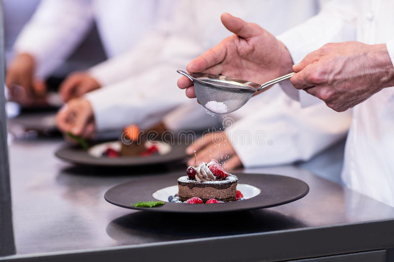 Close-up of chef finishing a dessert plate. With icing sugar in the kitchen stock images