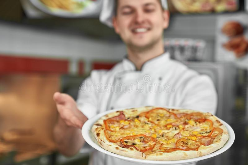 Close up of chef holding pizza on white plate. stock image