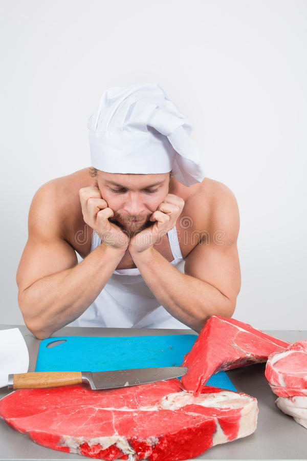 Close-up of chef in a nightcap with huge pieces of. Meat on the table. bodybuilder stock images
