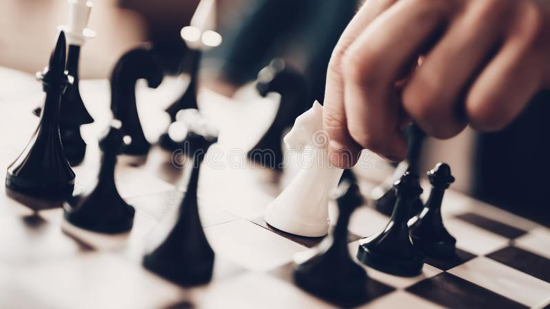 Close up chess board with white and black figures. Arab Businessman. Successful Young Man. Good Leisure. Arab playing chess. Man planning strategy. can`t make stock photography