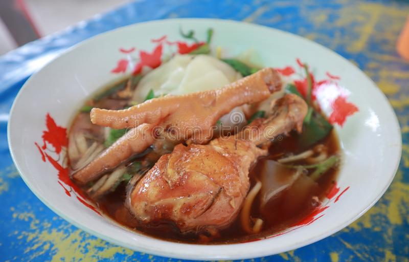 Close-up of chicken leg noodle in a soup with herbs and spices in Asian style cup. royalty free stock photo