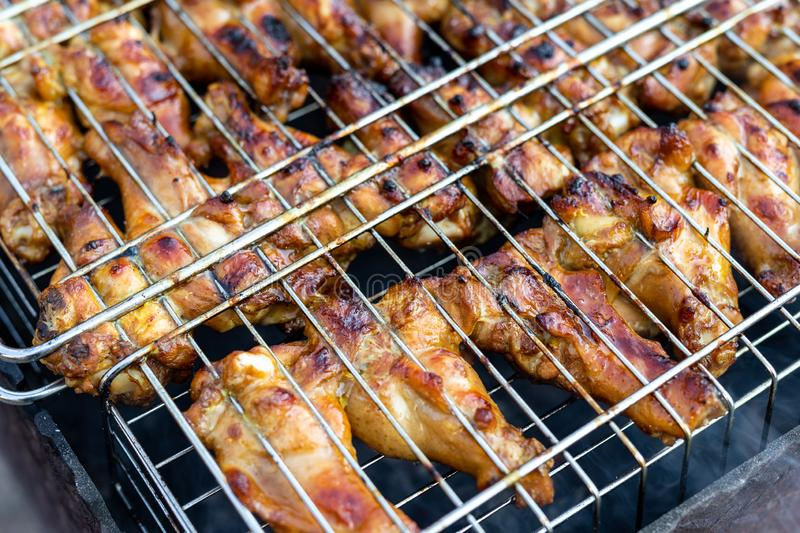 Close-up chicken wings cooking in metal barbecue grid on grill brazier. Outdoors weekend party on backyard. Tasty golden brown. Delicious bbq meal food meat hot stock photos
