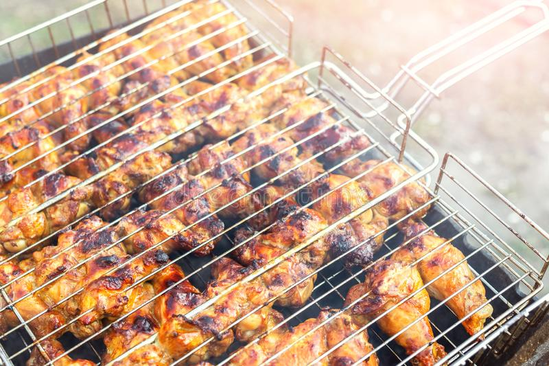 Close-up chicken wings cooking in metal barbecue grid on grill brazier. Outdoors weekend party on backyard. Tasty golden brown stock images