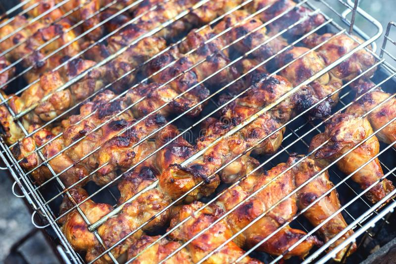 Close-up chicken wings cooking in metal barbecue grid on grill brazier. Outdoors weekend party on backyard. Tasty golden brown stock image