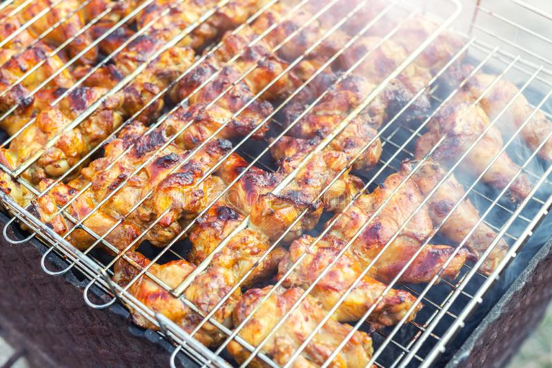 Close-up chicken wings cooking in metal barbecue grid on grill brazier. Outdoors weekend party on backyard. Tasty golden brown. Delicious bbq meal food meat hot stock photo