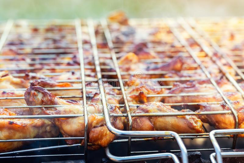Close-up chicken wings cooking in metal barbecue grid on grill brazier. Outdoors weekend party on backyard. Tasty golden brown. Delicious bbq meal food meat hot royalty free stock image