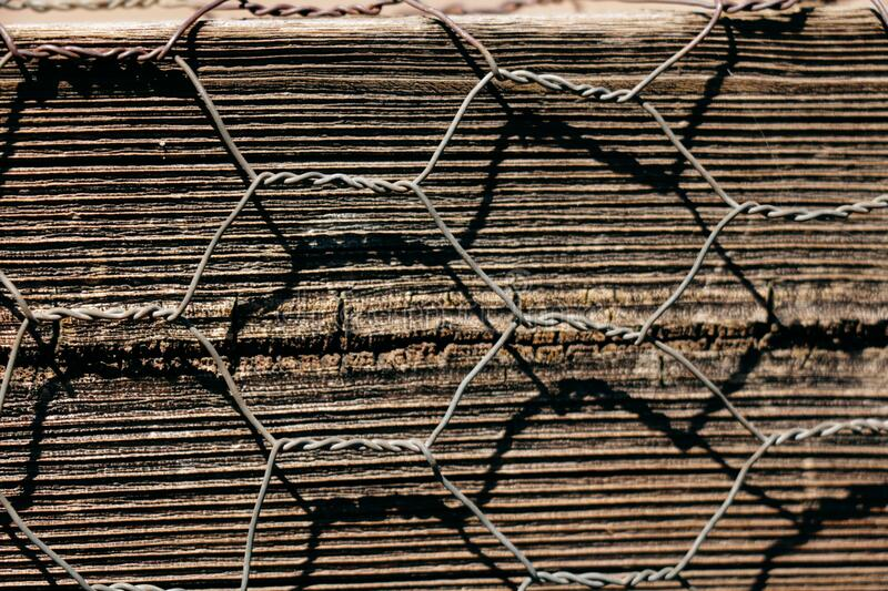 Close up on Chicken Wire across a wooden plant. Harsh light hits the twisted chicken wire creating a shadow over textured wooden plank royalty free stock photos