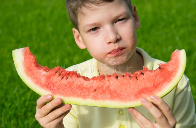 Close-up child boy eating a large slice of watermelon, staining his face, on a background of green grass royalty free stock images