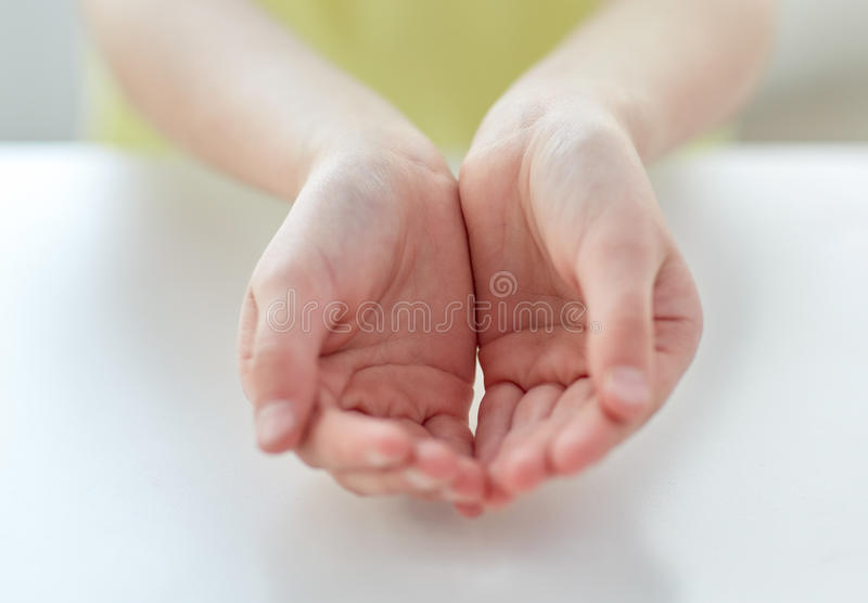 Close up of child cupped hands. People, charity, childhood and advertisement concept - close up of child cupped hands at home stock photo