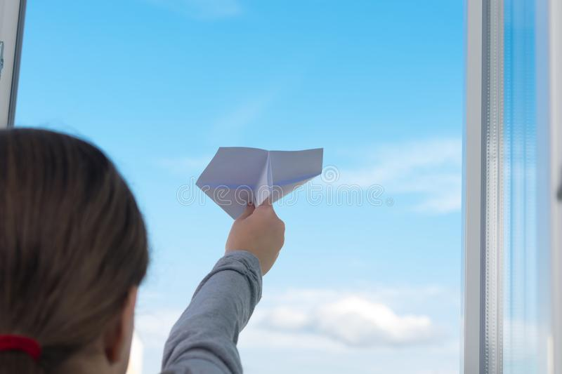 Close-up, a child girl, launches a paper plane from the window, against the sky, there is a place for the inscription stock image
