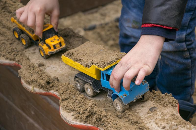 Little kid playing with toys. Close up of child hands holding miniature cars. Boy in casual clothes gaming in sandbox with scale models of trucks with grit stock photography