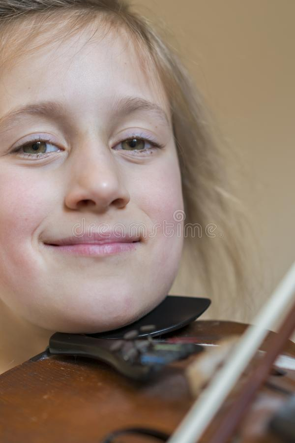 Close up of a child playing violin on isolated light background. Portrait of girl with string and playing violin. Portrait of the royalty free stock images