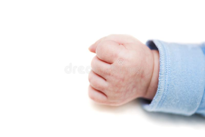 Close up of a child`s fist on white background. Clenched fist - hand of child, baby power. New born baby hand.  stock photography