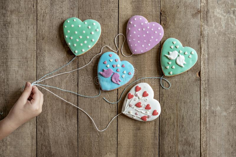 child`s hand holding gingerbread hearts for strings like balloons royalty free stock photography