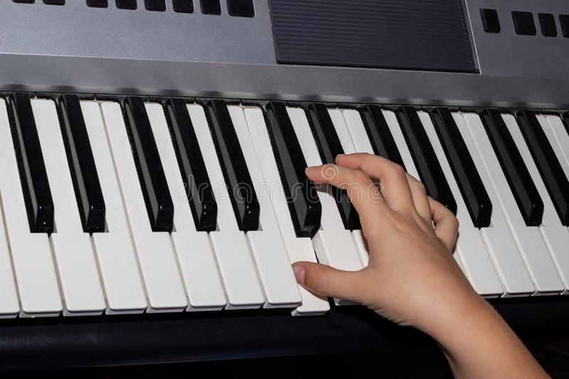 Close-up of a child`s hand playing a synthesizer. Hand of a child playing the piano keyboard stock photos