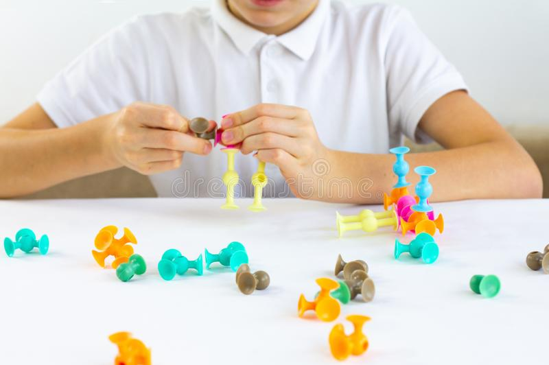 Close-up of child`s hands playing board game while sitting at the table at home, fine motor skills and creativity concept stock photography