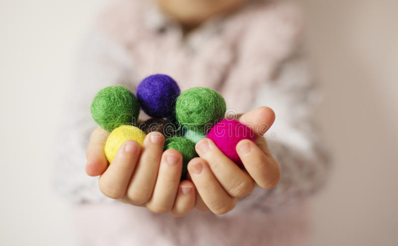 Close up of children hands holding colorful felt balls. Child, kid palms. A little girl keep in handfuls of colored wool balls royalty free stock images