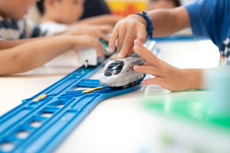 Close up of children hands playing, assembling the colorful plastic railway track. stock photo