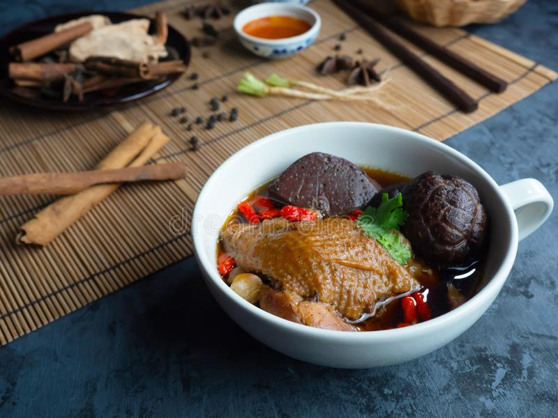Close-up of Chinese chicken soup in a white cup decorated with Chinese shiitake mushrooms, goji berries, chicken blood and stock photography