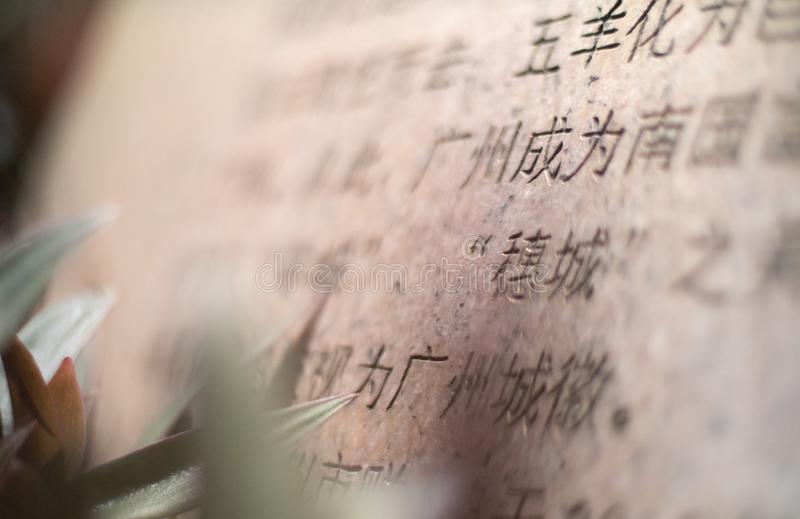 Close up of Chinese engraving on a stone tablet in the Seychelles. In shallow depth of field royalty free stock image