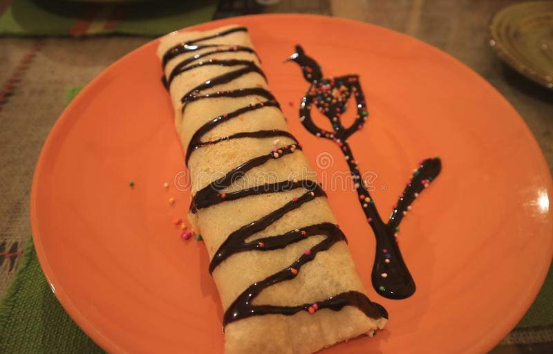 Close-up of Choco Banana Filling Crepe Decorated with Chocolate Sauce Served on Vibrant Orange Color Plate royalty free stock photos