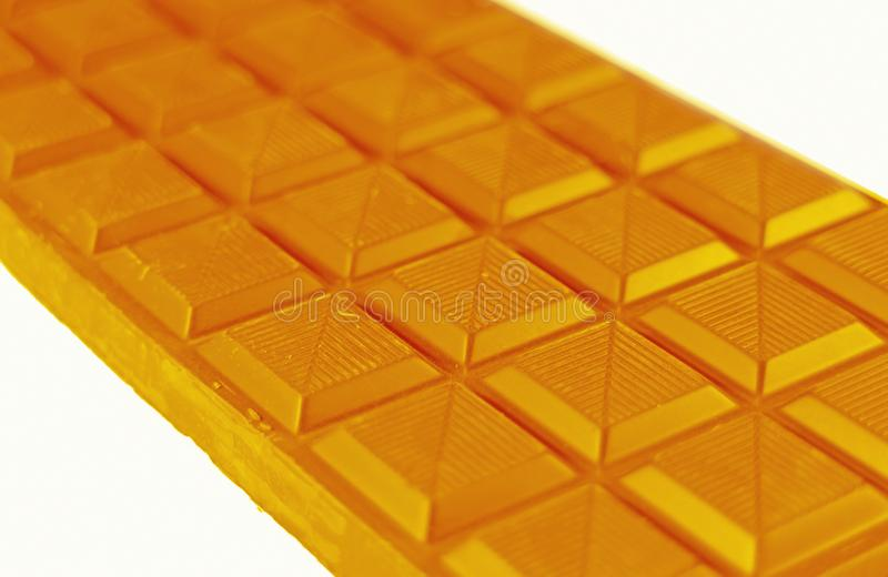 Close-up of Chocolate Bar in Honey Yellow Color Isolated on White Background royalty free stock photography