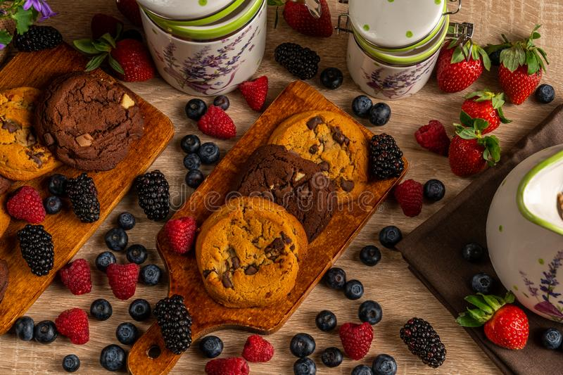 Close up of chocolate cookies with mix of forest fruits with ceramic vessels on wooden table royalty free stock images