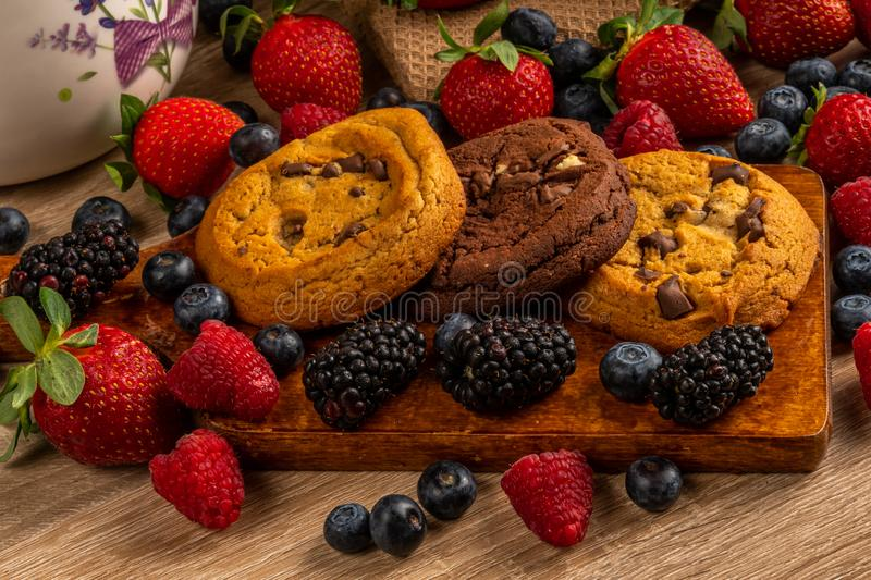 Close-up chocolate cookies on wooden cutting board with forest fruits stock photo