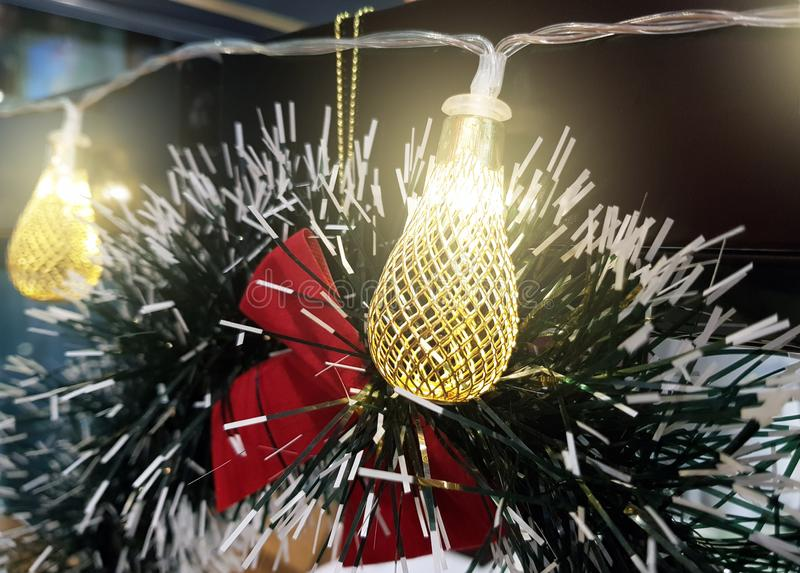 Close up christmas accessories hanging on decorated with lights Christmas tree. Christmas decorations on a spruce branch, copy stock image