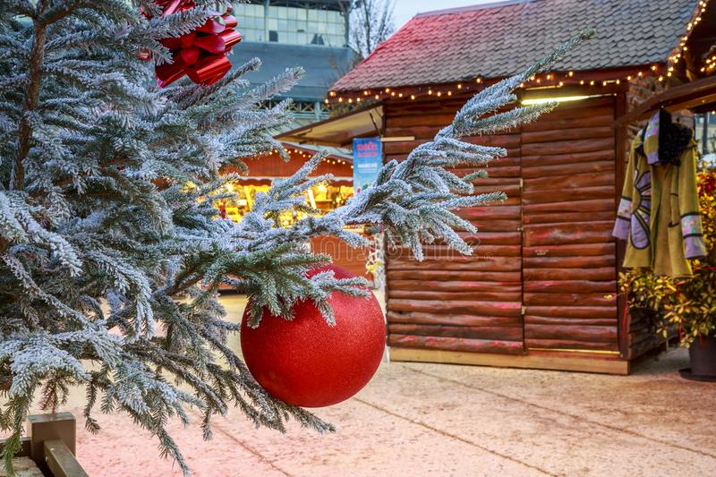 Close-up of a Christmas ball hanging on a snowy tree with Christmas market chalets in the backgr. Niort, France - December 05, 2017:Close-up of a Christmas ball royalty free stock images