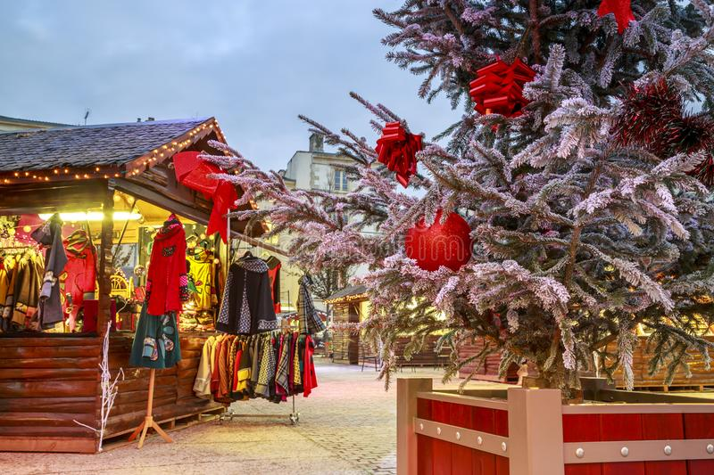 Close-up of a Christmas ball hanging on a snowy tree with Christmas market chalets in the backgr. Niort, France - December 05, 2017:Close-up of a Christmas ball stock photo
