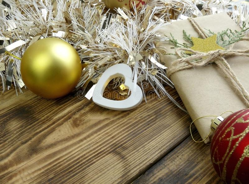 Close up Christmas decoration with gift, baubles and tinsel on wooden background. royalty free stock photos