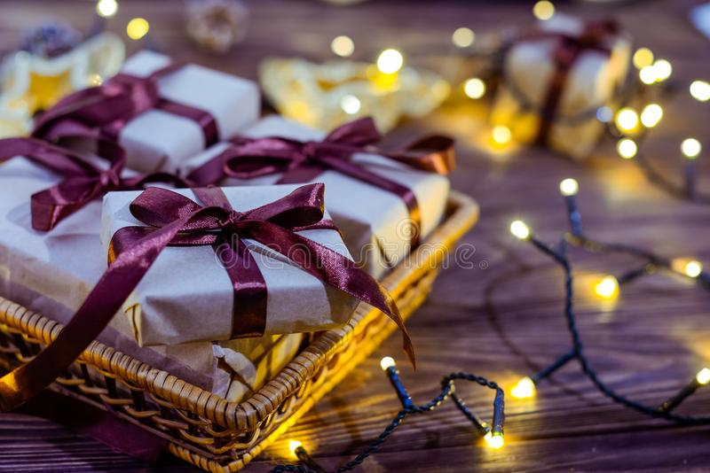 Close up christmas gift boxes in craft paper with satin ribbons and holiday decorations on the dark wooden background. Christmas a. Nd New year concept royalty free stock photography
