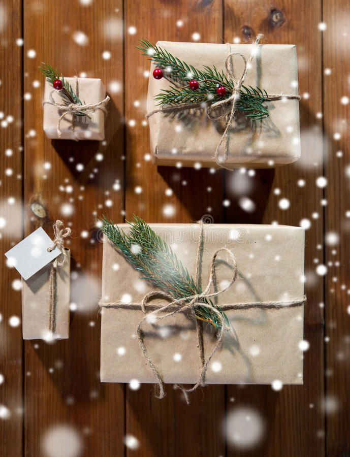 Close up of christmas gifts with fir brunch. Christmas, holidays, presents, new year and decor concept - close up of gift boxes wrapped into brown mail paper and royalty free stock photo