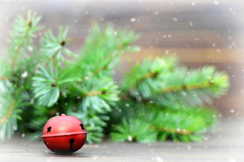 Christmas jingle bell and Christmas tree branches royalty free stock photography